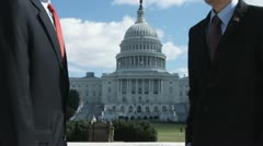 CU of one man suspiciously passing a document another in front of the US Capitol - stock footage
