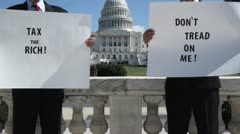 SLO MO, MS of two men holding protest signs in front of the US Capitol Building, Stock Footage