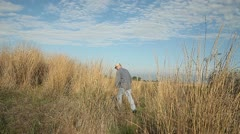 Walking away in dry grasses Stock Footage