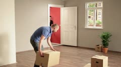WS of three people moving boxes out of a house Stock Footage