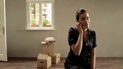 MS, PAN of a woman talking on a mobile amidst cardboard boxes Stock Footage