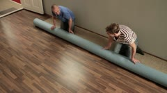 Stock Video Footage of MS, HA of two men unrolling a carpet