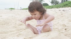 MS, A young girl playing in the sand on a beach Stock Footage