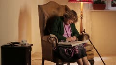 WS, TU, TD of a senior woman doing a crossword puzzle in the newspaper - stock footage