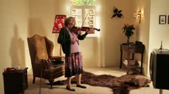 WS, PAN of a senior woman playing violin while her neighbor plays guitar, split - stock footage