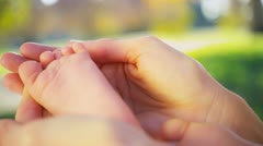 Close up Gentle Hands Cradling Baby Foot Stock Footage