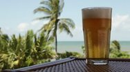 MS Lockdown of a glass of cold beer on a table and a beach in the background Stock Footage