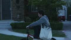 SLO MO, TS, MS, paperboy riding his bike past houses Stock Footage