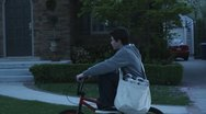 Stock Video Footage of SLO MO, TS, MS, paperboy riding his bike past houses