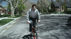 TS, MS, boy riding his bike down a street, front view Stock Footage