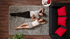 MS, Lockdown, couple lying on a rug talking and holding hands, overhead view Stock Footage