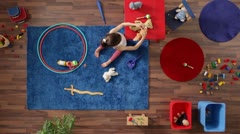 MS, Lockdown, young girl playing in a room with a lot of toys, overhead view Stock Footage