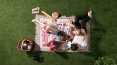 MS, Lockdown, a playful family relaxing on a blanket at a park, overhead view Stock Footage