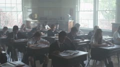 ZI, MS, A class of school children finishing a test and leaving Stock Footage