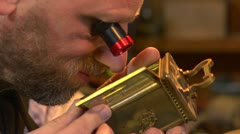 Clockmaker examining a carriage clock prior to restoration Stock Footage