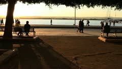 One couple and one man sitting on bench overlooking ocean Stock Footage