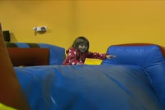 Girl Playing on Inflatable Obstacle Course Stock Footage