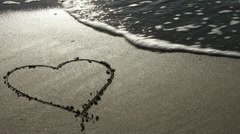 Heart drawn in the sand (with wave) Stock Footage