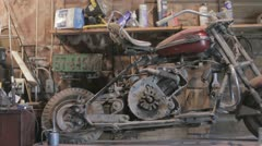 Old motorcycle sitting in shed Stock Footage
