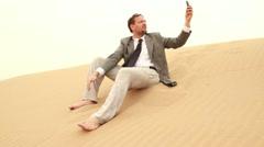 Businessman searching for signal on cellphone in the desert HD Stock Footage