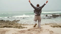 Excited businessman running to the sea, slow motion HD Stock Footage
