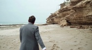 Stock Video Footage of Exhausted businessman walking and undressing on the sea shore HD