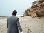 Stock Video Footage of Exhausted businessman walking and undressing on the sea shore NTSC