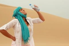 Thirsty woman drinkig water from bootle in the desert NTSC Stock Footage