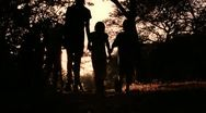 Children Walking Holding Hands into Sunset Stock Footage