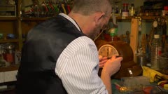 Clockmaker fitting the hands on a clock, over shoulder. Stock Footage