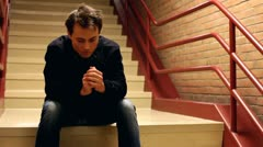 Upset man thinking while sitting on steps Stock Footage