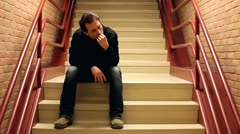 Nervous man chewing nails on steps Stock Footage