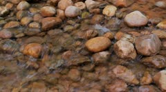 Water rushing over river rocks in stream Stock Footage