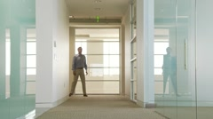 Businessman poking out of office hallway Stock Footage