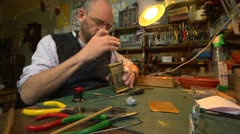 Clockmaker working on a carriage clock - wide shot of bench Stock Footage