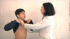 Pediatrician listens with a stethoscope chest teen Stock Footage