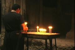 Armenia Man lights candels at Geghard Stock Footage