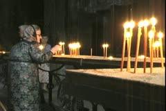 Armenian woman lights candles at Geghard Monastery - stock footage