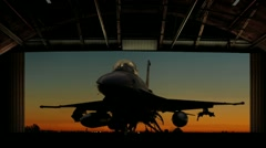 An F-16 Fighting Falcon is revealed as hangar doors open slowly. - stock footage