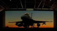 Stock Video Footage of An F-16 Fighting Falcon is revealed as hangar doors open slowly.