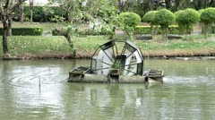 A water wheel floating on the pond in a puplic park - stock footage