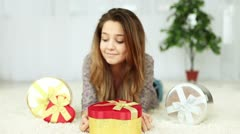 Happy teenager with a gift lying on the floor Stock Footage