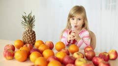 Child drinking orange juice at the table Stock Footage