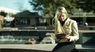 Stock Video Footage of businesswoman with tablet sitting by a fountain
