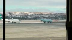 WestJet on runway taxiing, viewed from inside terminal. - stock footage