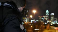 A night time lapse of a photographer taking pictures of the Charlotte Skyline Stock Footage