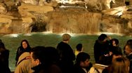 Tourists throwing coin into Trevi Fountain in Rome, Italy at night Stock Footage
