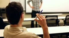 Bored student flicking pen while someone talks Stock Footage