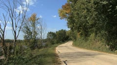 Iowa road by river wind and leaves blowing Stock Footage