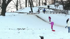 Children playing on snow mountain in park ProRes Stock Footage